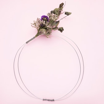 Bouquet of flower tied on metallic wire ring for frame on pink background