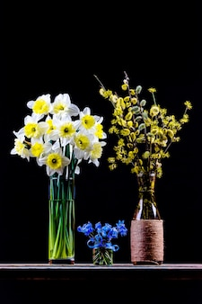 Bouquet of flowering branches of willow and dogwood in a vase, bouquet of narcissus flower and bouquet of bluebell flower in a vase