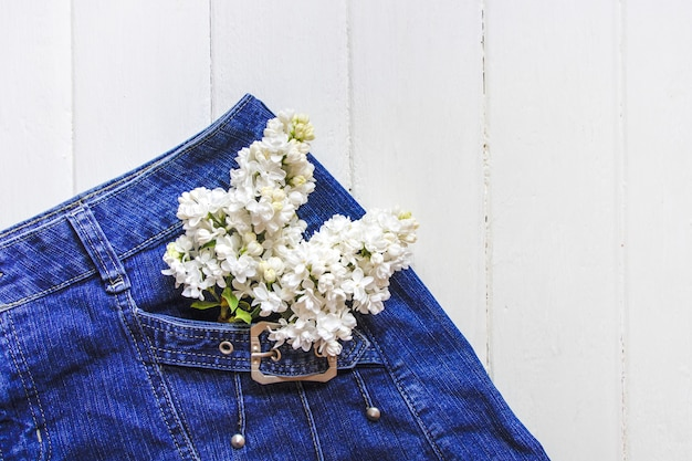 Bouquet of flowers in blue jean pocket. space for text