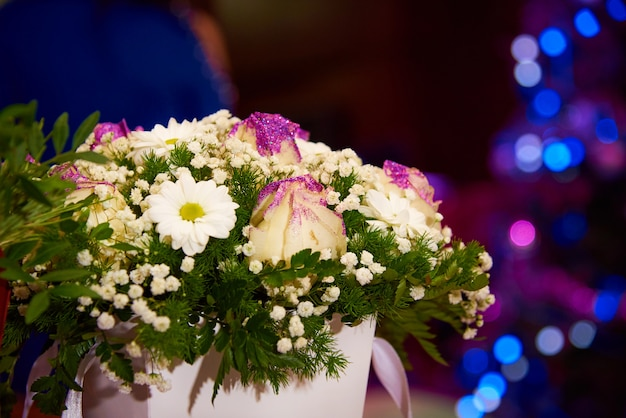 A bouquet of flowers in a box on the background of bright multi-colored bokeh.