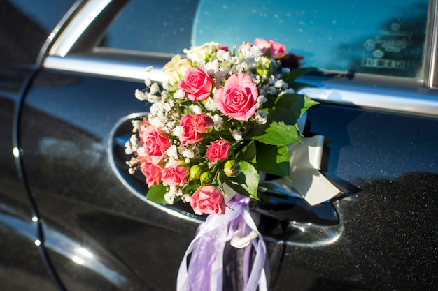 A bouquet of flowers on a car door