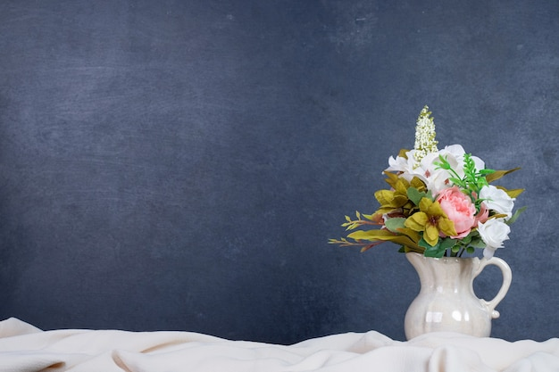 Bouquet of flowers in ceramic vase on dark wall with copyspace.