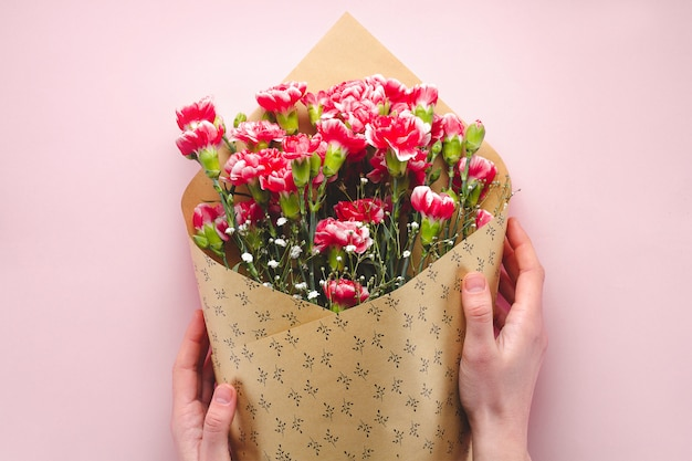 A bouquet of flowers in craft paper on a pink background. floristry. florist holding a bouquet of fresh carnations.