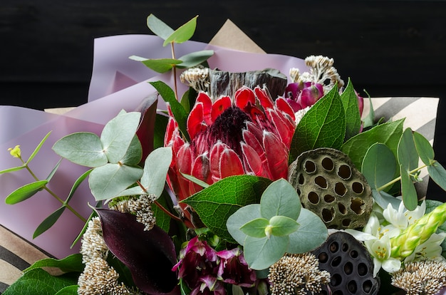 A bouquet of flowers on a dark wooden background. bouquet with protea, orchid, poppy, succulent..