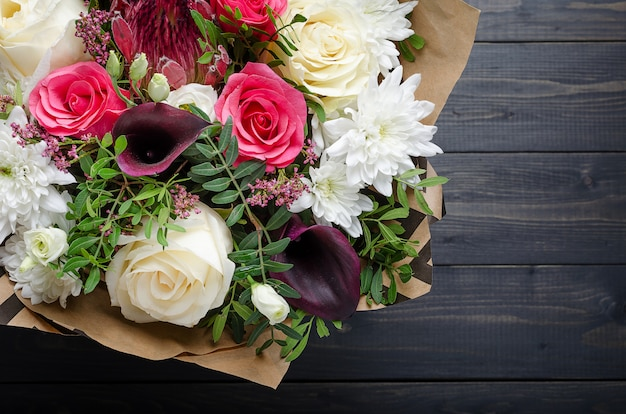 A bouquet of flowers on a dark wooden background. bouquet with roses.