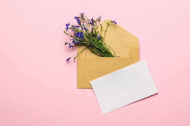 A bouquet of flowers in an envelope and a sheet of white paper on a pink background. flat lay.