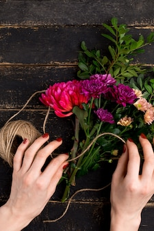 Bouquet of flowers in female hand on a black wooden table
