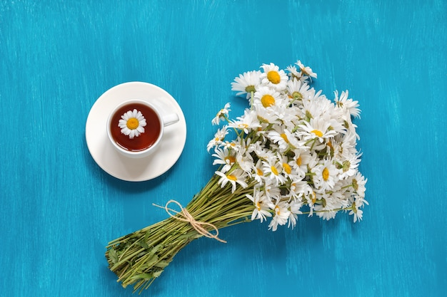 Bouquet flowers field chamomiles cup of herbal tea on blue woode