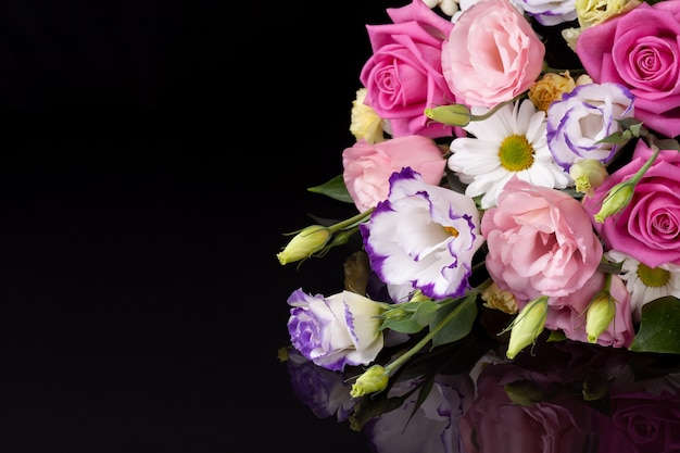 A bouquet of flowers from roses, lisianthus, daisies, chrysanthemums with a reflection