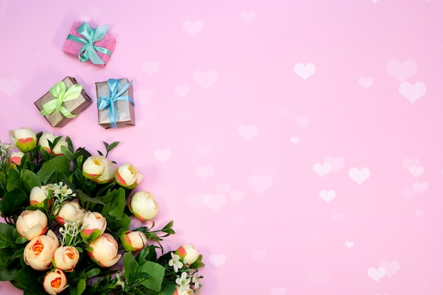 Bouquet of flowers and gift boxes on pink background with heart lights.
