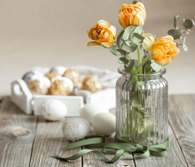Un mazzo di fiori in un vaso di vetro con elementi decorativi su uno sfondo sfocato. concetto di vacanza di pasqua.