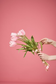 A bouquet of flowers in hand and a gift romance summer pink background