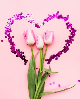 Bouquet of flowers in heart frame on pink background