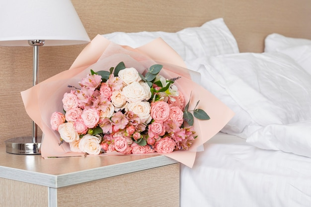 Bouquet of flowers on the hotel bedside bed
