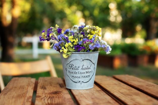 庭の木製テーブルにヴィンテージの花瓶の花束の花。パティオヤードの居心地の良い装飾