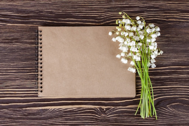 Bouquet of flowers lily of the valley and empty paper notebook on brown wooden rustic table from above, top view, space for text, flat lay.