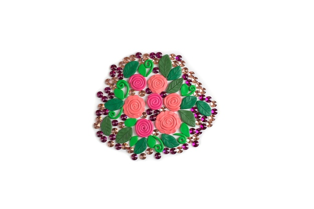 Bouquet of flowers made of plasticine on a white background roses and leaves flat lay