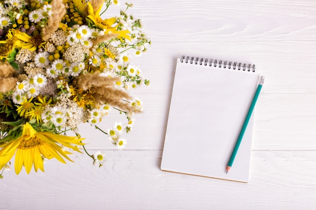 Bouquet of flowers, notebook and pencil on a white table.