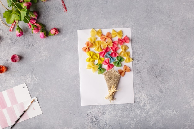 Bouquet of flowers out of colored paper and colored pasta.