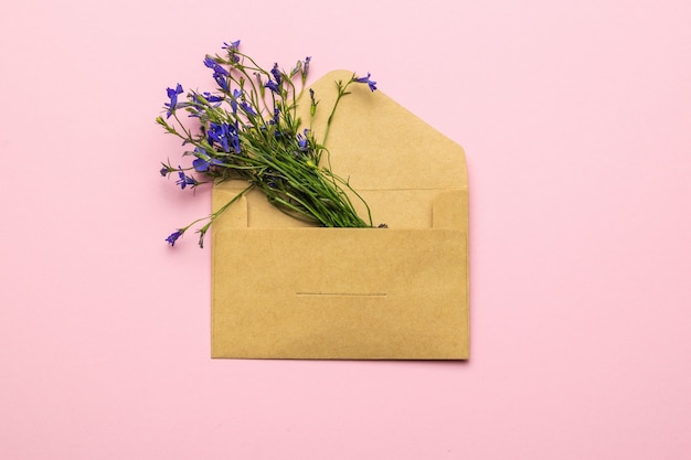 A bouquet of flowers in a paper postal envelope on a pink background. flat lay.
