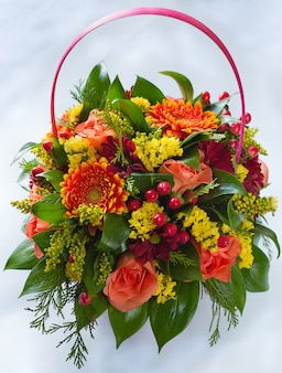 Bouquet of flowers in  pink basket on a light background