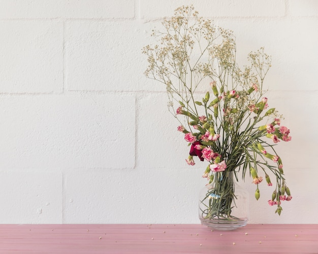 Bouquet of flowers and plant twigs in vase near wall