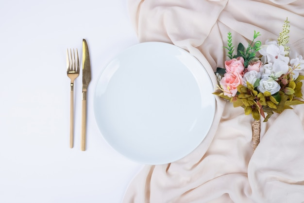 Bouquet di fiori, piatto e posate sulla superficie bianca.