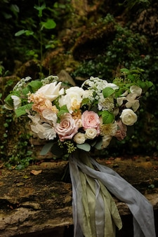 A bouquet of flowers provides the backdrop for two wedding rings