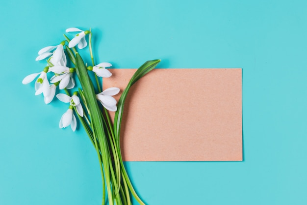 Bouquet of flowers of snowdrops and craft paper for notes on blue background flat lay top view