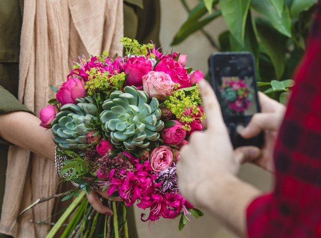Bouquet of flowers and suculents in the hands of a women, mobile shooting from aside