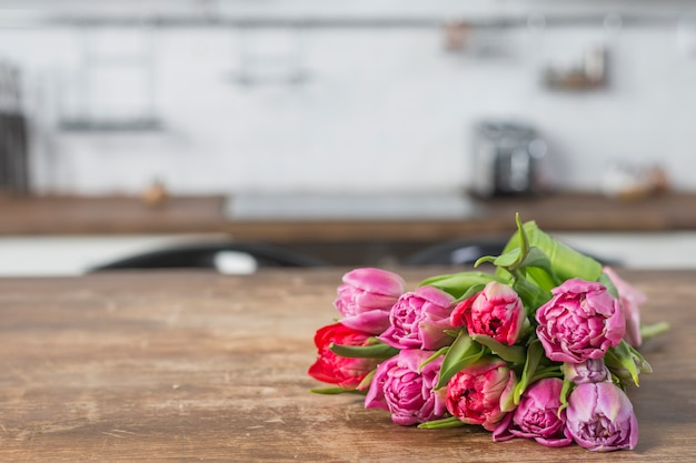 Bouquet of flowers on table in kitchen