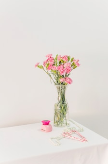 Bouquet of flowers in vase near candy canes, box and beads on table
