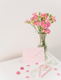 Bouquet of flowers in vase near candy canes, envelope and beads on table