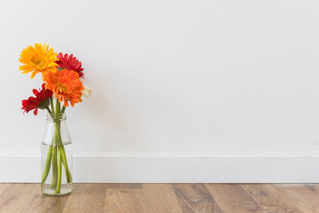 Bouquet of flowers in vase near wall