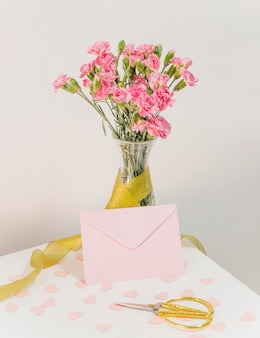 Bouquet of flowers in vase with ribbon near envelope, scissors and paper hearts