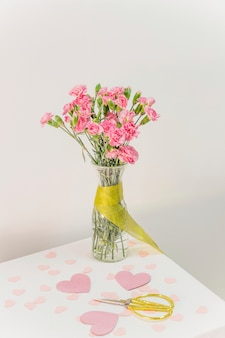 Bouquet of flowers in vase with ribbon near scissors and paper hearts