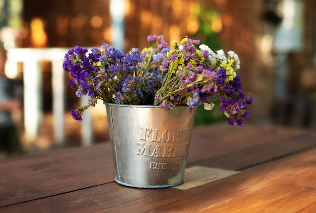 Bouquet flowers in vintage vase on wooden table in garden. cozy decor of patio yard