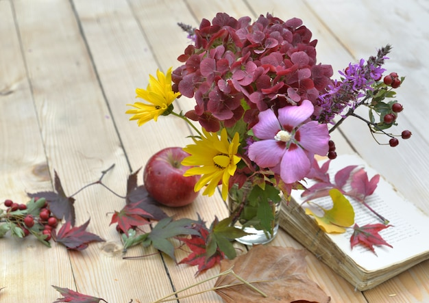 Bouquet of flowers with beautiful autumnal colors on a table in leaves