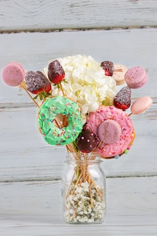 Bouquet of flowers with donuts and macarons