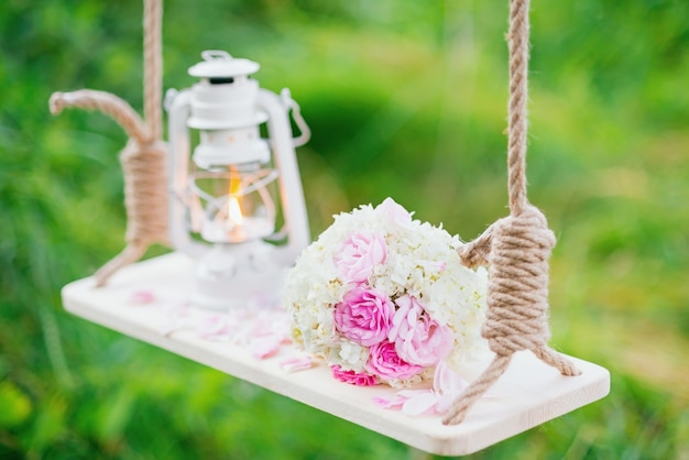 A bouquet of flowers with a kerosene lamp on the swing in the forest