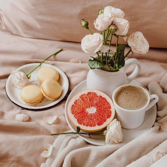 Bouquet of flowers with morning coffee and grapefruit on bed