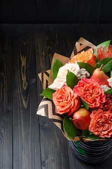 Bouquet of flowers with pears on a dark wooden background. fruit bouquet.
