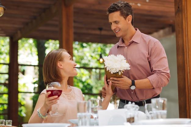 아내를위한 꽃다발. 아내에게 꽃다발을 선물하면서 매우 흥분된 잘 생긴 남자를 빛나는