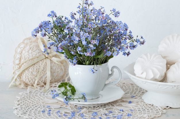 A bouquet of forget-me-not flowers on a table in a white cup, a heart made of lace