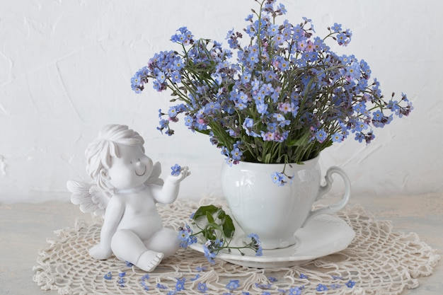 A bouquet of forget me not flowers on a table in a white cup and a white angel