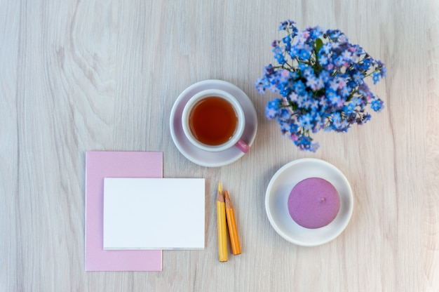 A bouquet of forget-me-not flowers on a table with a cup of tea and card for congratulation text. holiday background, copy space, soft focus, top view.