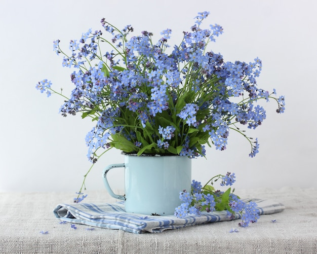 Bouquet of forget-me-nots in a blue mug. delicate summer composition.