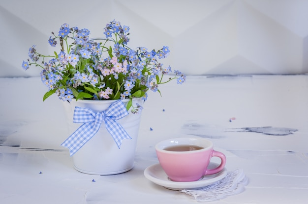 Bouquet of forget-me-nots in metal bucket and and cup of tea on white background.