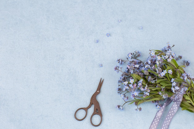 A bouquet of forget me nots, scissors and a ribbon