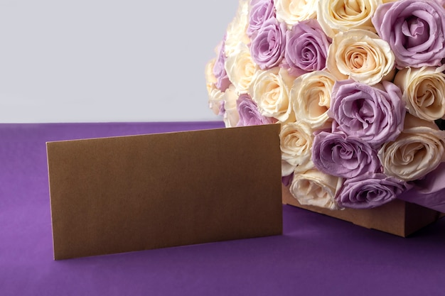 Bouquet of fresh amazing white and purple roses and craft envelope.